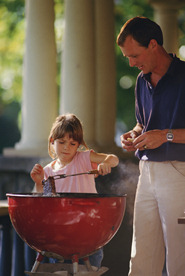 Father allowing daughter to grill
